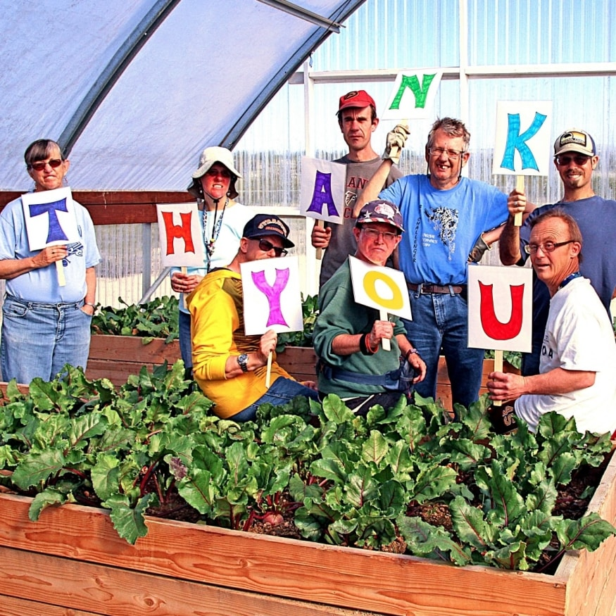 Ranchers hold Thank You signs for supporters of Rainbow Acres