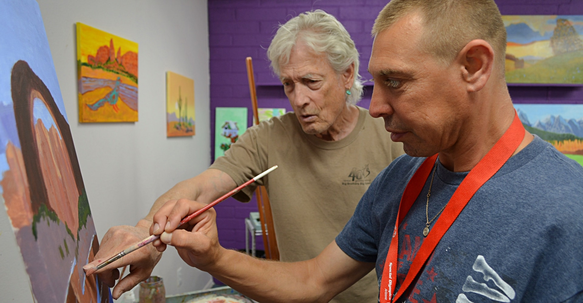 Instructor with student learning to paint in fine arts program at Rainbow Acres