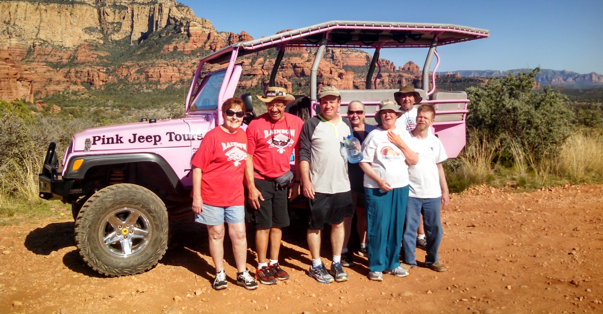 Group exploring desert red rocks with pink jeep