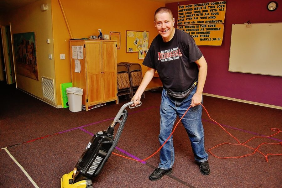 Man doing janitorial work using vacuum cleaner