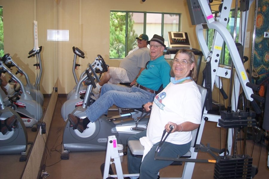 3 adults using exercise machines inside fitness center