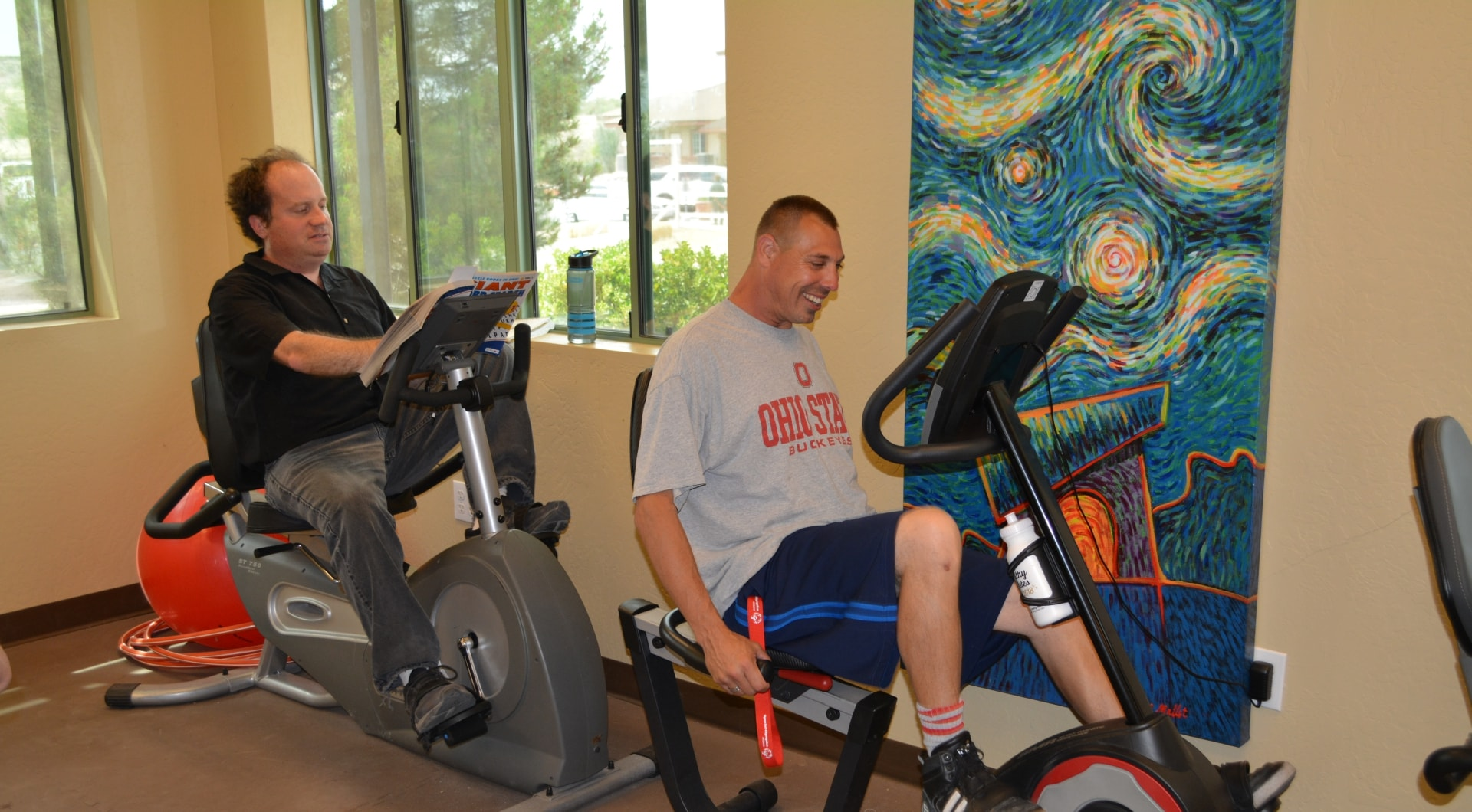 Exercise bikes being used by two adults with developmental disabilities