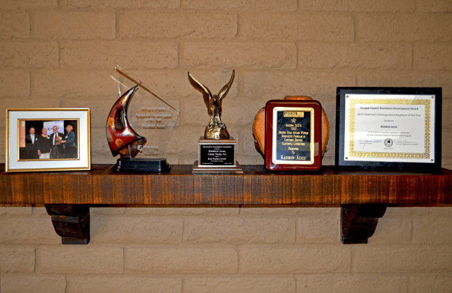 Recent awards received by Rainbow Acres on display shelf