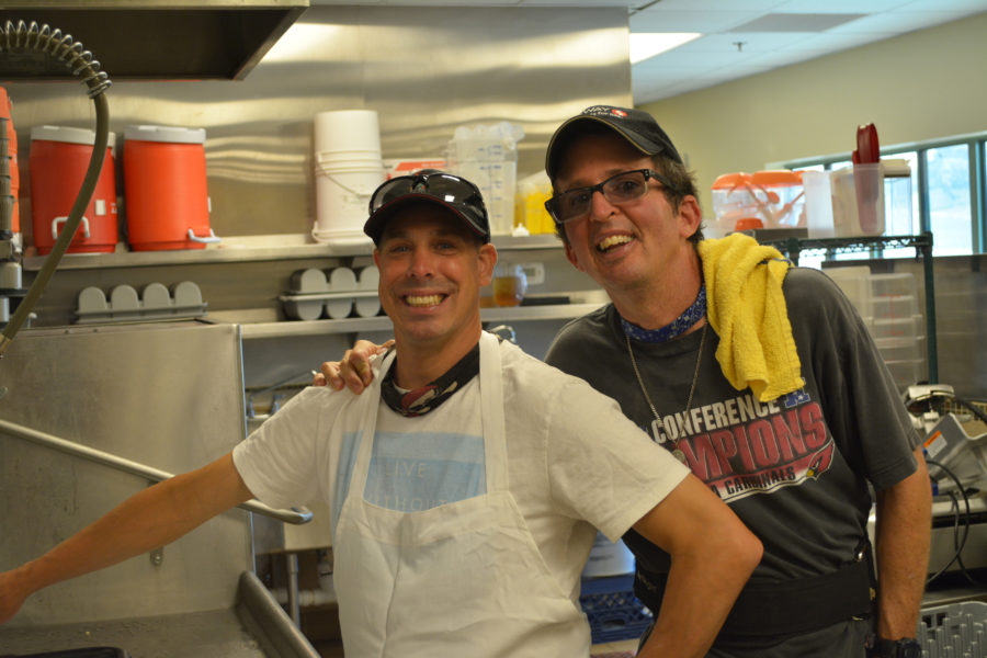 Two happy people working together in kitchen at Rainbow Acres